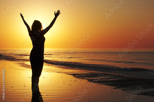 Woman with open arms at the sunset