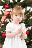 kleines Mädchen vor dem Weihnachtsbaum