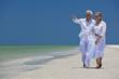 Happy Senior Couple Walking Pointing To Sea on Tropical Beach
