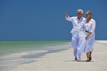 Happy Senior Couple Walking Pointing To Sea on Tropical Beach