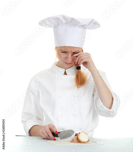 crying female cook in white uniform cutting onion