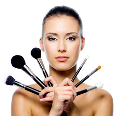 Beautiful woman with makeup brushes - isolated