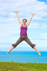 Beautiful young woman jumping and laughing by the ocean