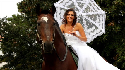 Bride sitting on a horse in the park