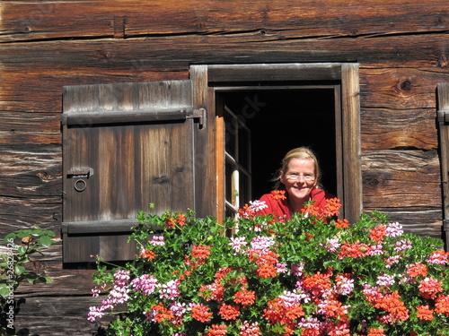Frau an Fenster an altem Bauernhaus