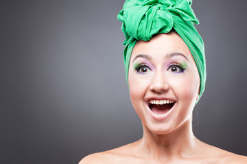 Happy excited woman with pink-green makeup in green hat