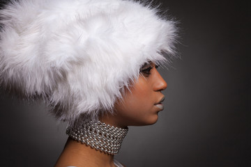 Profile of african woman in white hat and silver necklace
