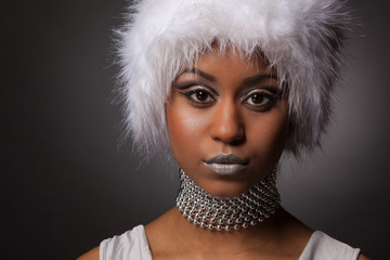 Confident african glamour woman in white hat and silver makeup