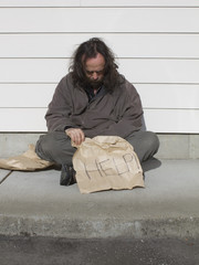 Poor man sitting on sidewalk with help sign
