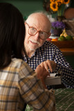 Elderly man in home with care provider or survey taker poster