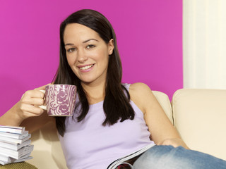 Young Woman Drinking Coffee Reading a Magazine. Model Released