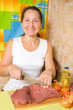 Mature woman is cooking beef