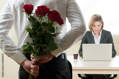 Excited and surprised businesswoman receiving red roses