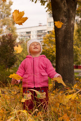 Beautiful baby girl watching leaves' dance
