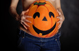Halloween pumpkin painted on belly of pregnant