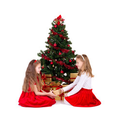 Two little girls sit near Christmas tree.