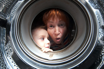 woman and boy peer into get washer