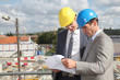 Architects checking plan on construction site