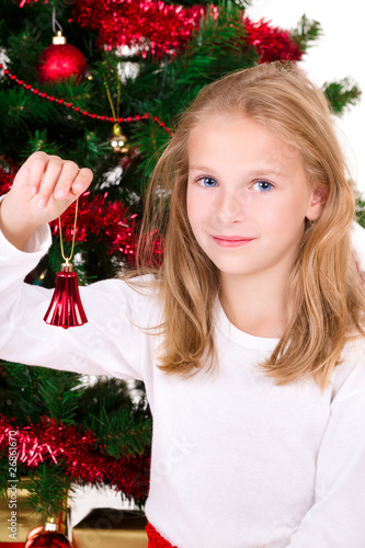 Young girl with bell sit near Christmas tree.