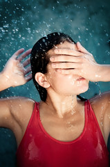 Girl covering face from water droplets