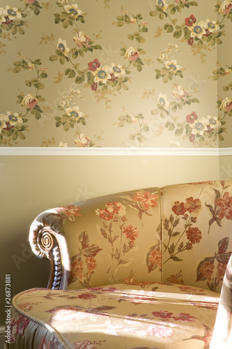 part of vintage chair with flowers standing near the wall