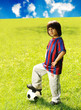 Young excited boy standing with the  ball in the grass outdoors
