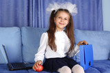 schoolgirl girl with laptop, backpack and red apple in sofa
