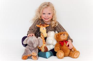 kleines blondes Mädchen mit Stofftieren