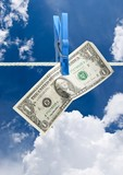 U.S. dollar on rope over blue sky background