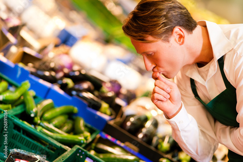 Man in supermarket as shop assistant