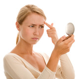 Fototapety Woman finding an acne on her forehead