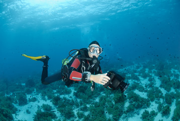 Female scuba diver and underwater video equipment.