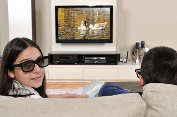 Sister and brother watching 3d film on TV