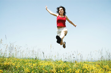 Beautiful young girl jumping in a meadow