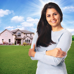 Young woman standing in front of house smiling