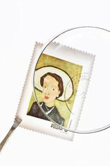 Postage stamp under magnifier with tweezers