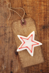 christmas white star candy on retro paper tag, wooden backgroun