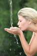 Blond woman drinking water from fountain
