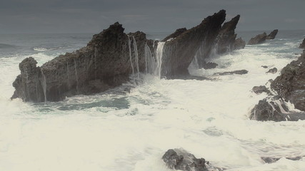 big sea wave splashing on the rocks