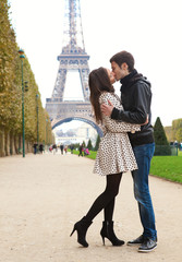 Young romantic couple kissing near the Eiffel Tower in Paris