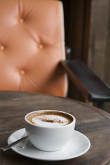 A cup of Cappuccino with orange armchair background