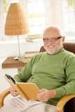 Portrait of happy pensioner relaxing with book poster
