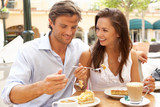 Fototapety Young Couple Enjoying Coffee And Cake In Cafe