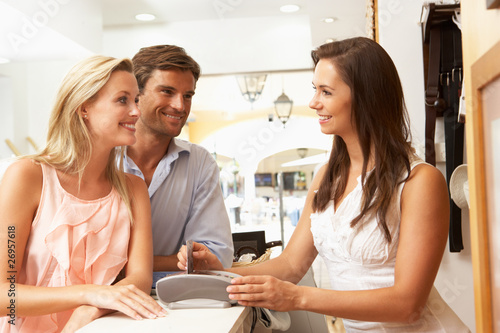 Female Sales Assistant At Checkout Of Clothing Store With Custom