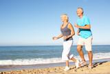 Fototapety Senior Couple In Fitness Clothing Running Along Beach