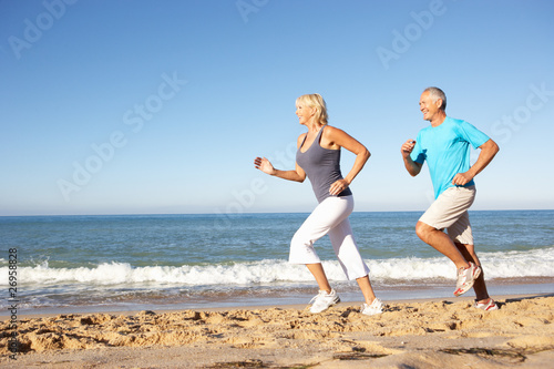 Senior Couple In Fitness Clothing Running Along Beach - 26958828