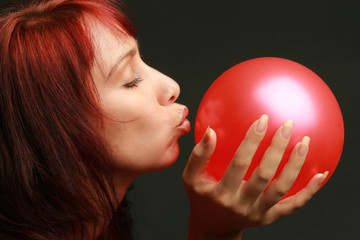 Careful concept. Woman with red balloon on black.