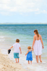 Family walking along tropical beach