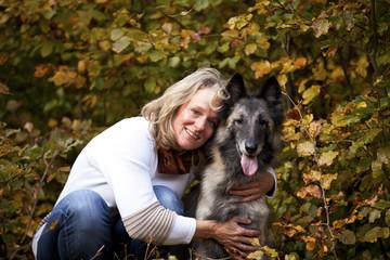 lächelnde blonde Frau mit ihrem belgischen Schäferhund
