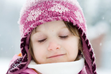 Beauty toddler girl with snowflakes on long eyelashes